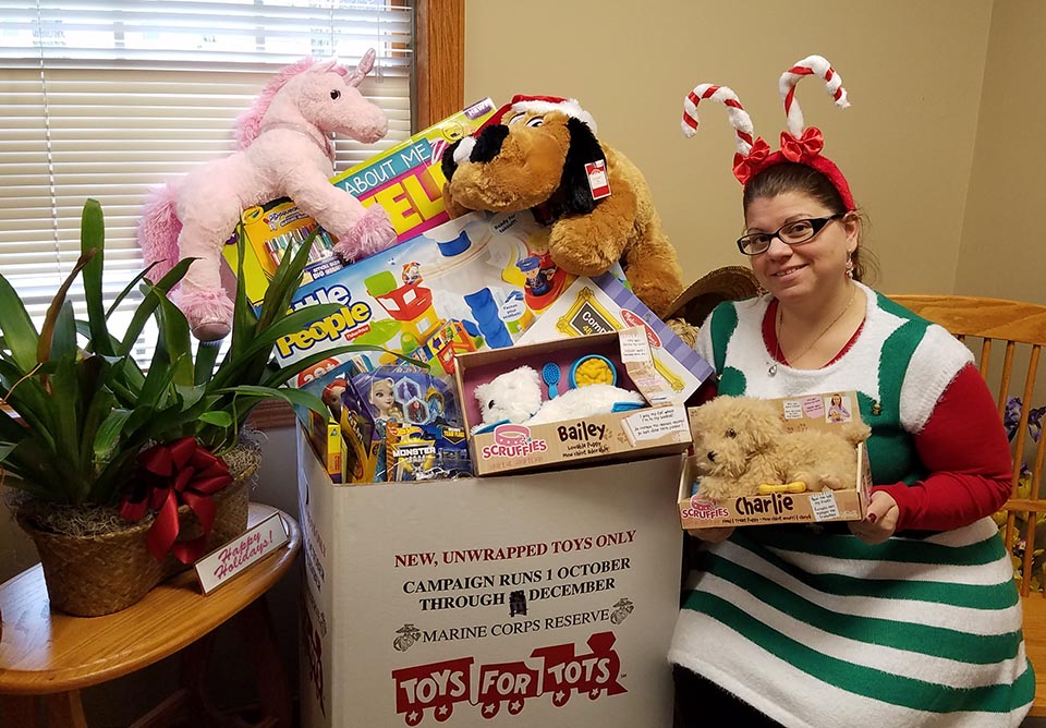 IQ employee April Rak displaying the toys collect for Toys for Tots in 2016.